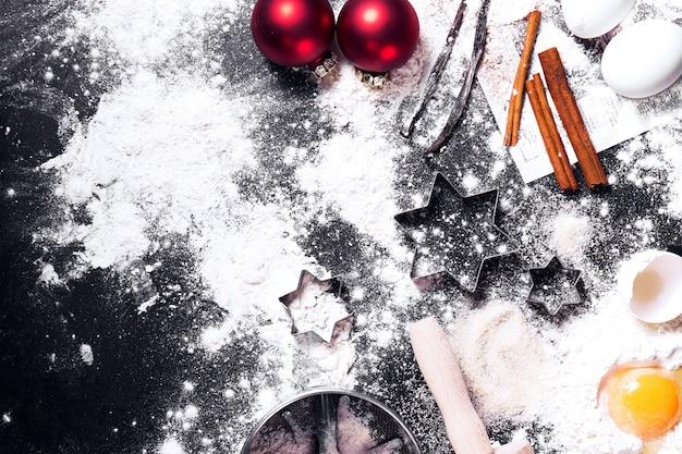 Schwarz tisch voller mehl und eier mit weihnachtsdekorationen