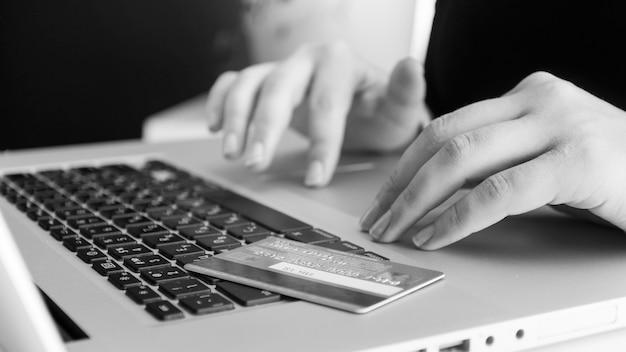 Schwarz-weiß-ansicht der kreditkarte, die auf der laptoptastatur liegt. konzept des online-shoppings und des e-commerce.