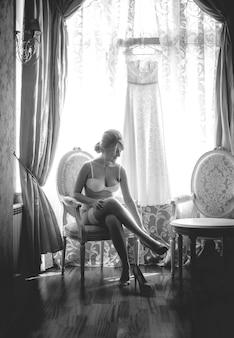 Schwarz-weiß-aufnahme einer sexy braut, die auf einem stuhl sitzt und strümpfe anzieht