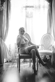 Schwarz-weiß-aufnahme einer sexy braut in dessous, die auf einem stuhl gegen das fenster sitzt