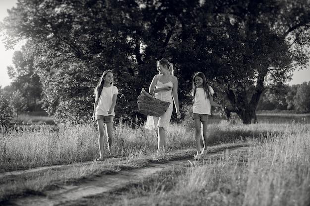 Schwarz-weiß-bild der glücklichen mutter mit töchtern, die auf der wiese spazieren gehen