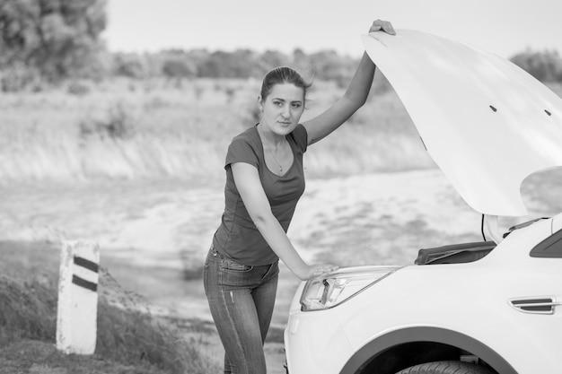 Schwarz-weiß-bild der jungen frau, die die motorhaube des kaputten autos am straßenrand öffnet