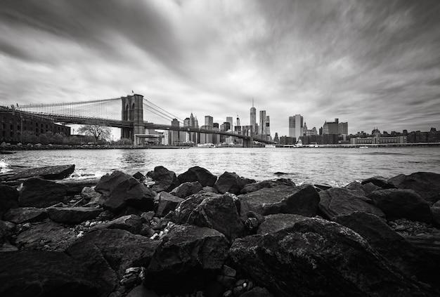 Schwarz-weiß-bild der skyline von manhattan mit brooklyn bridge. felsen und steine am ufer des east river. manhattan-skyline von dumbo