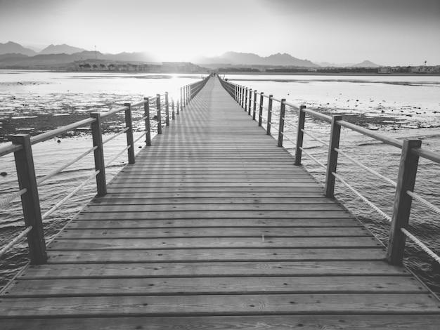 Schwarz-weiß-bild der untergehenden sonne über den meereswellen und dem langen holzsteg