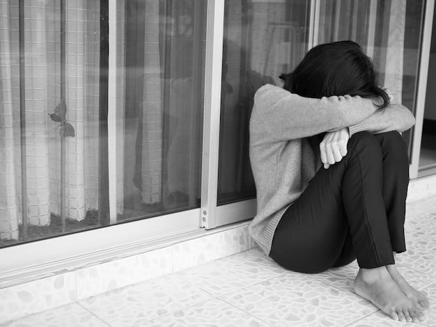 Schwarz-weiß-bild des sitzenden schreis der frau. sie enttäuscht, strapaziert, bedauert von liebhabern problem ehemann sie. unerwidert verliebt.