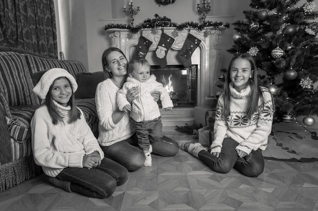Schwarz-weiß-bild einer glücklichen großen familie, die zu weihnachten auf dem boden am kamin sitzt