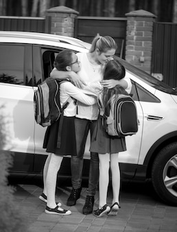 Schwarz-weiß-bild einer glücklichen mutter, die ihre beiden töchter küsst, nachdem sie sie von der schule getroffen hat
