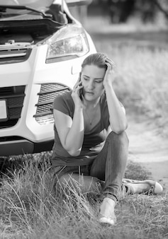 Schwarz-weiß-bild einer jungen frau, die auf dem boden sitzt und sich auf ein kaputtes auto stützt