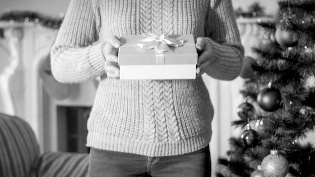 Schwarz-weiß-bild einer jungen frau, die eine weihnachtsgeschenkbox hält und sie in der kamera zeigt