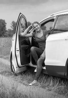 Schwarz-weiß-bild einer schönen lächelnden frau, die auf dem autofahrersitz am feld sitzt