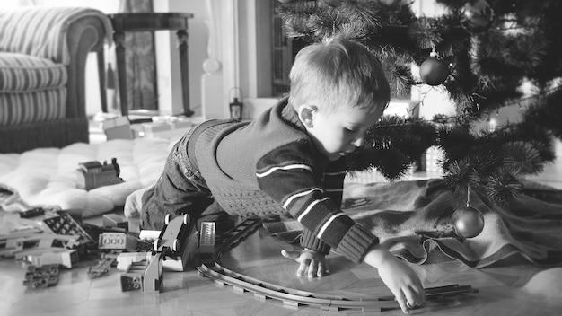Schwarz-weiß-bild eines 4 jahre alten kleinen jungen, der mit spielzeugeisenbahn und zug auf dem boden im wohnzimmer unter dem weihnachtsbaum spielt