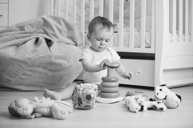 Schwarz-weiß-bild eines entzückenden babys, das auf dem boden spielt