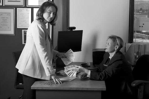 Schwarz-weiß-bild von zwei russischen geschäftsfrauen in anzügen, die israelische banknoten und us-dollar-geld im modernen büro austauschen. geschäft, finanzen, währungsfonds. weibliche hand, die banknoten hält