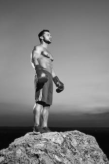 Schwarz-weiß-flachwinkelaufnahme eines gutaussehenden jungen, starken, muskulösen athletischen mannes, der boxhandschuhe trägt und nachdenklich wegschaut, nachdem er im freien trainiert hat.