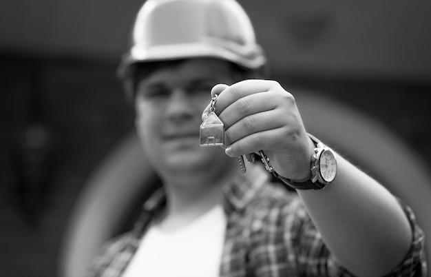 Schwarz-weiß-foto des gebäudemanagers, der schlüssel vom neuen haus gibt