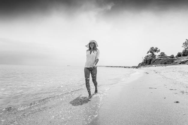 Schwarz-weiß-foto einer fröhlichen frau, die am sandstrand spazieren geht