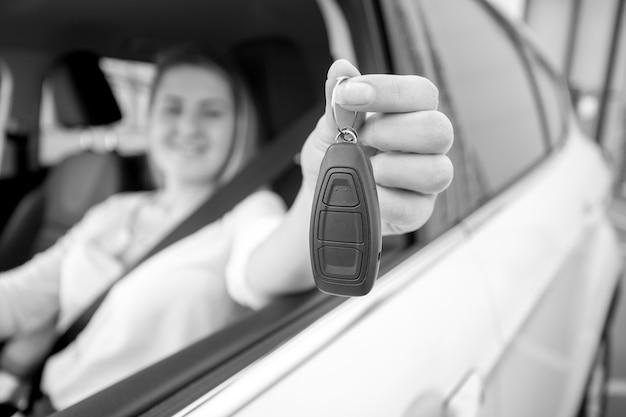 Schwarz-weiß-foto einer glücklichen frau, die autoschlüssel durch offenes fenster zeigt