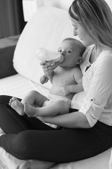Schwarz-weiß-foto einer schönen mutter, die ihr baby auf dem bett füttert