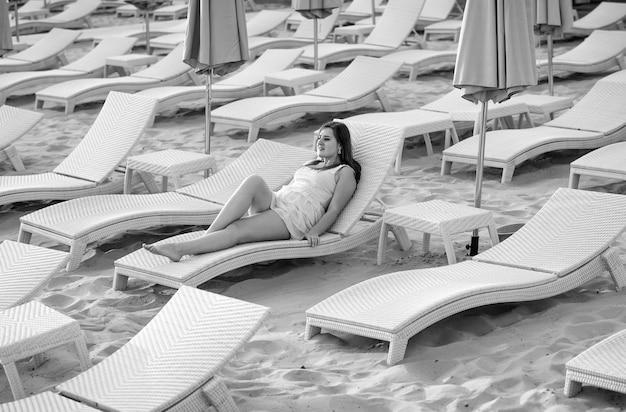 Schwarz-weiß-foto einer sexy frau im kleid, die auf der sonnenliege liegt