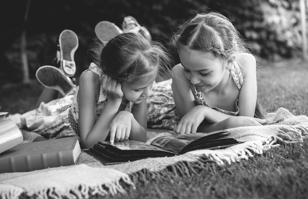 Schwarz-weiß-foto von jungen mädchen, die sich das familienfotoalbum ansehen