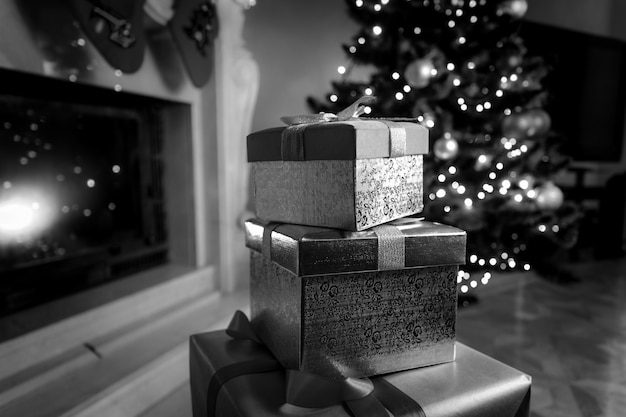Schwarz-weiß-foto von weihnachtsgeschenkboxen, die auf dem boden neben dem kamin liegen