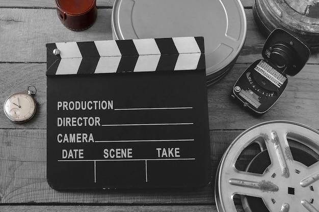 Schwarz-weiß-klappe, filmrollen, taschenuhr und belichtungsmesser von oben auf einem holzbrett
