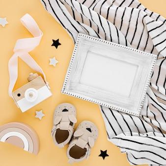Schwarz-weiß-musselin-saddle-decke mit fotorahmen und babypantoffeln, spielzeug auf gelbem hintergrund. set mit geschlechtsneutralem neugeborenenzubehör. flache lage, ansicht von oben