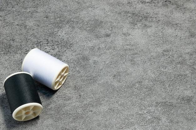 Schwarz-weiß-nähgarn auf steinhintergrund mit kopierraum