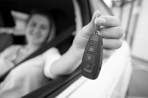 Schwarz-weiß-nahaufnahmefoto einer glücklichen frau, die autoschlüssel durch offenes fenster zeigt