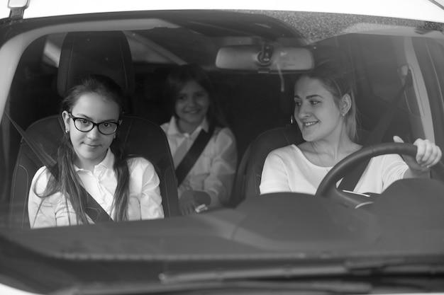 Schwarz-weiß-porträt der glücklichen mutter und zweier töchter, die nach der schule mit dem auto nach hause fahren