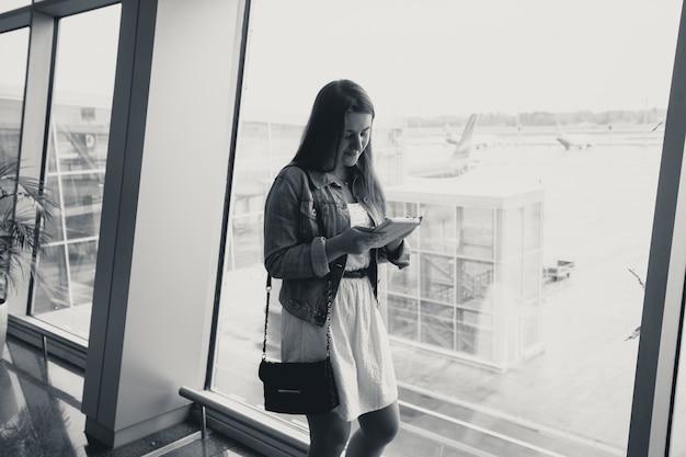 Schwarz-weiß-porträt der jungen frau mit digitalem tablet am flughafen