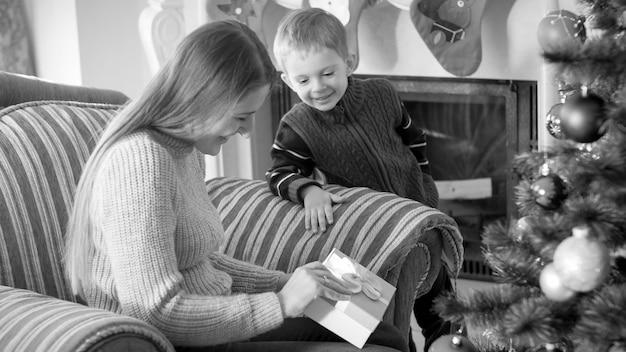 Schwarz-weiß-porträt der jungen mutter mit ihrem kleinen sohn, der eine schachtel mit weihnachtsgeschenken und geschenken öffnet