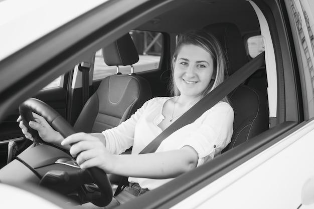 Schwarz-weiß-porträt der lächelnden frau, die auto fährt
