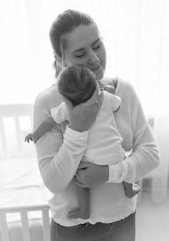 Schwarz-weiß-porträt der schönen jungen mutter, die mit ihrem baby posiert