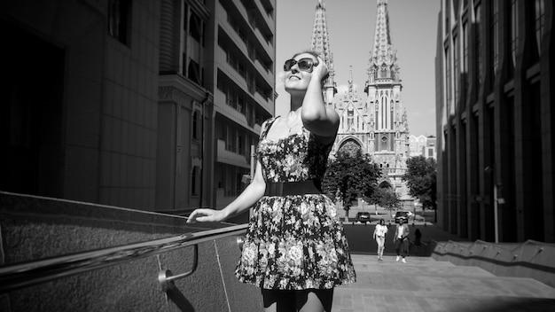 Schwarz-weiß-porträt einer schönen lächelnden jungen frau in kurzem kleid, die auf den straßen der alten europäischen stadt mit modernem bürogebäude und alten kirchen spaziert