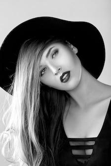 Schwarz-weiß-porträt einer schönen sexy frau mit schwarzem hut