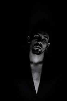 Schwarz-weiß-porträt eines ernsten mannes mit schwarzem hintergrund