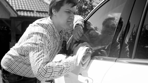 Schwarz-weiß-porträt eines stilvollen jungen mannes, der die fenster seines autos putzt.