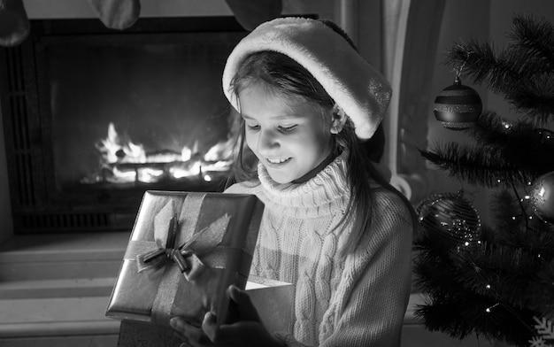 Schwarz-weiß-porträt eines süßen, fröhlichen mädchens in weihnachtsmütze, das in die weihnachtsgeschenkbox schaut