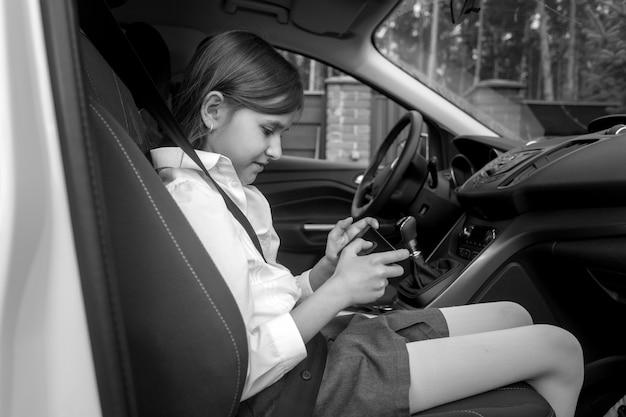 Schwarz-weiß-porträt eines süßen mädchens, das im auto sitzt und auf dem smartphone spielt