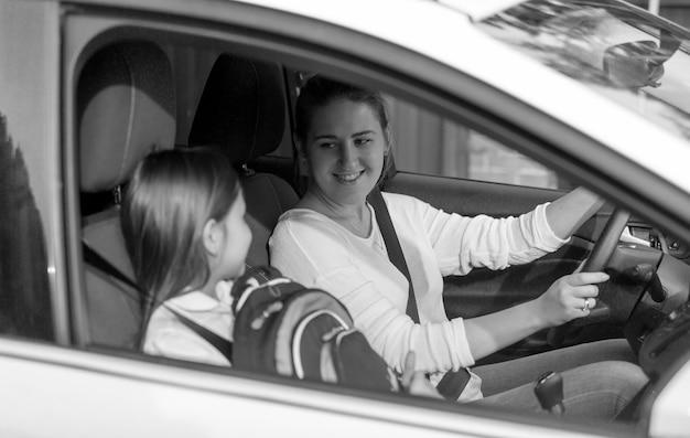 Schwarz-weiß-porträt eines süßen mädchens, das mit der mutter mit dem auto zur schule geht