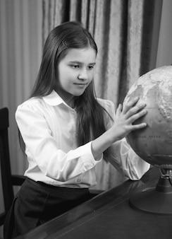 Schwarz-weiß-porträt eines süßen schulmädchens, das einen großen globus betrachtet