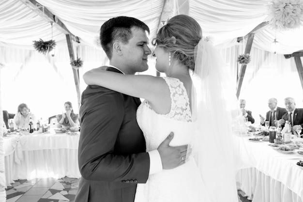 Schwarz-weiß-porträt von glücklichen jungvermählten, die im restaurant tanzen