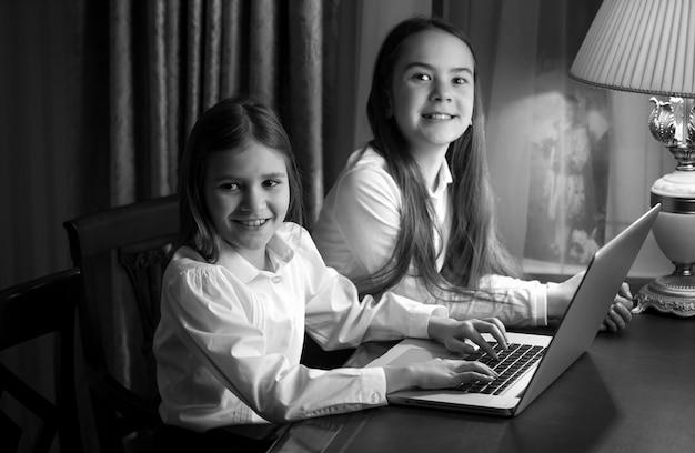 Schwarz-weiß-porträt von zwei kleinen schwestern mit laptop