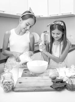 Schwarz-weiß-porträt von zwei lächelnden mädchen, die kuchen kochen und teig machen
