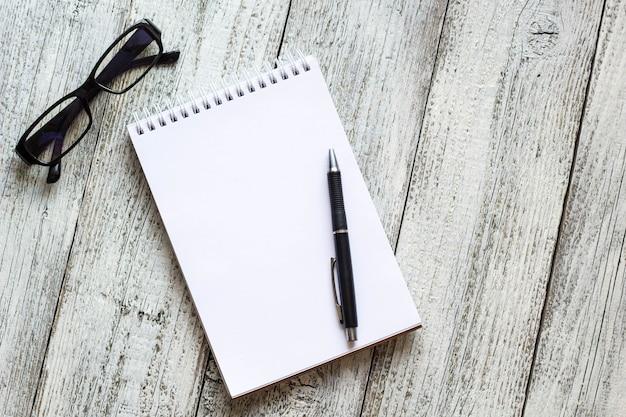 Schwarz-weiß-stillleben: geöffneter leerer notizblock, notizbücher, stift, bleistift, brille, geldbörse.