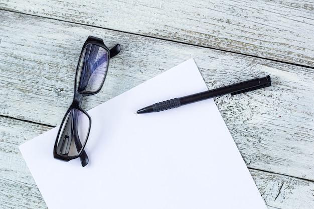 Schwarz-weiß-stillleben: geöffneter leerer notizblock, notizbücher, stift, brille.