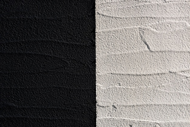 Schwarz-weiße betonwand in einem modernen stil, beleuchtet mit weichem licht und abwechselnd hochreliefierter oberfläche.
