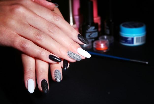 Schwarz-weiße nail art maniküre. feiertagsart helle maniküre mit scheinen. beauty hände. stylische nägel, nagellack