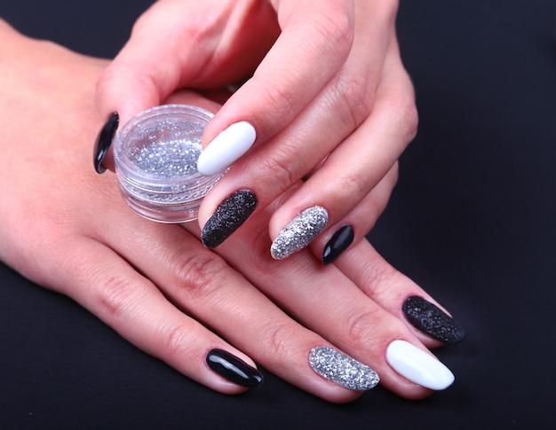 Schwarz-weiße nail art maniküre. feiertagsart helle maniküre mit scheinen. flasche nagellack. beauty hände. stylische nägel, nagellack